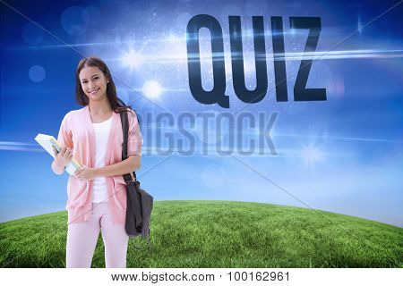The word quiz and pretty student smiling at camera against green hill under blue sky