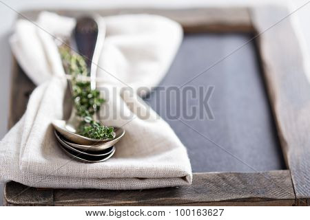 Tablespoons with a napkin and thyme