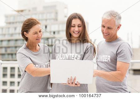 Smiling volunteers using laptop together on roof of building