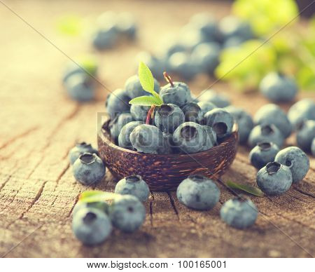 Freshly picked Blueberries in bowl on wooden table. Blueberry closeup. Concept of healthy eating. Bilberries in Vintage toned