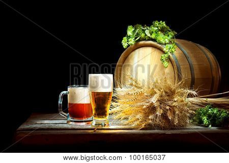 Beer concept. Wooden Barrel and two mugs with beer and fresh hop with ears of wheat isolated on black background. Beer production ingredients. Unbottled beer over dark. Traditions of brewing