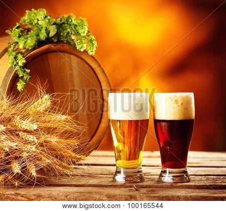 Beer barrel and two beer glasses with green hop and ears of wheat on wooden table. Dark and light beer. Brewery concept. Brewing traditions
