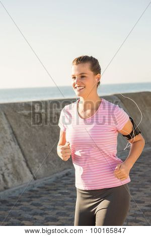 Smiling sporty blonde jogging with headphones at promenade