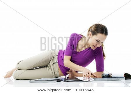 Young woman lying on the floor reading a magazine on white background studio