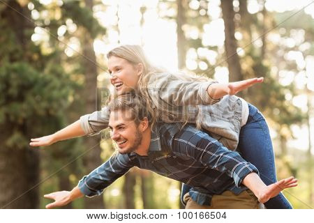 Smiling handsome man giving piggy back to his girlfriend in the nature