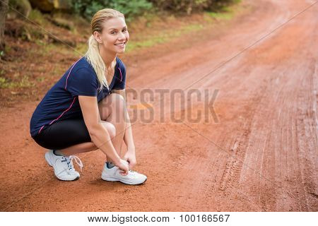 Portrait of smiling athletic blonde tying her shoelace in the nature