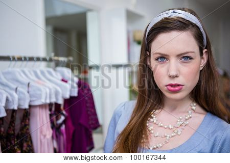 Brunette pouting at the camera in fashion boutique