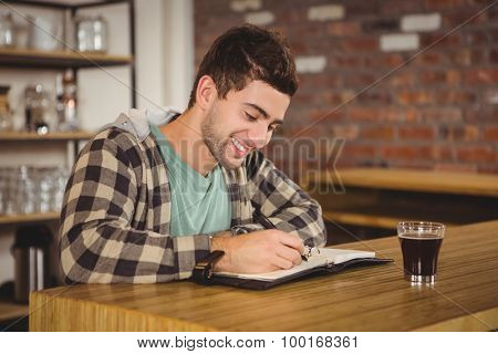 Smiling hipster having coffee and writing in planner at coffee shop