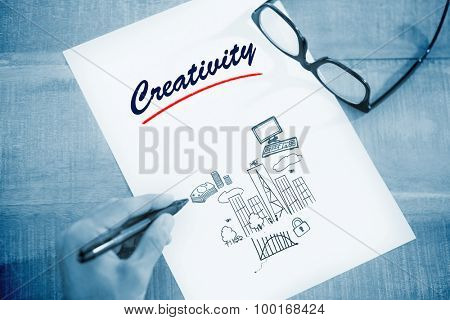 The word creativity and left hand writing on white page on working desk against business and cityscape