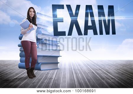The word exam and smiling student holding textbook against stack of books against sky