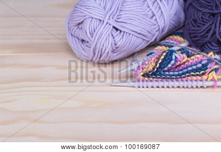 needles and skeins of yarn on a wooden table