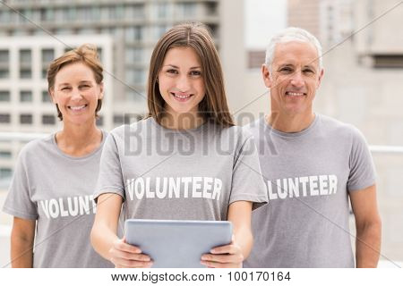 Portrait of smiling volunteers with tablet on roof of building