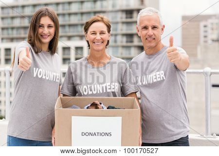 Portrait of smiling volunteers with donation box doing thumbs up on roof of building