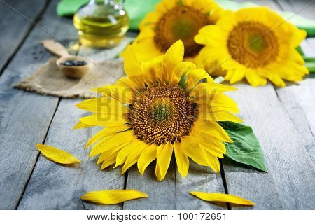 Beautiful bright sunflowers with bottle of oil on wooden table close up