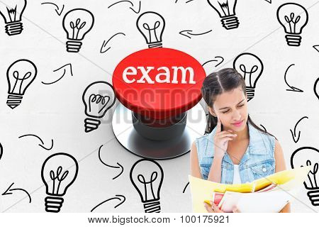 The word exam and student studying from folders against digitally generated red push button