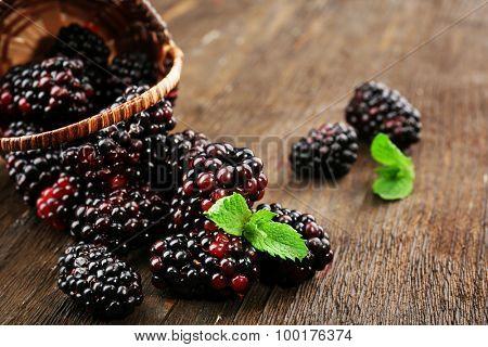Ripe blackberries with green leaves in wicker basket on wooden table, closeup