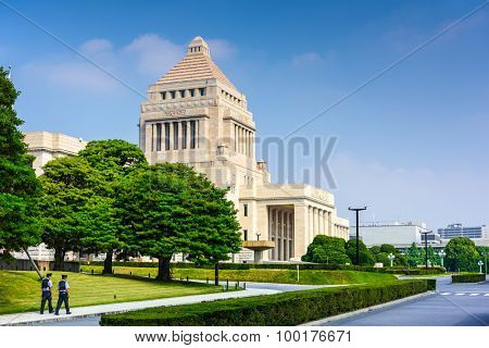 TOKYO, JAPAN - JULY 31 2015: Police walk below The National Diet Building of Japan. It is the place where both houses of the National Diet of Japan meet.