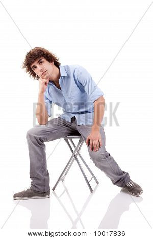 Young Man, Sitting On A Bench, Isolated On White  Background