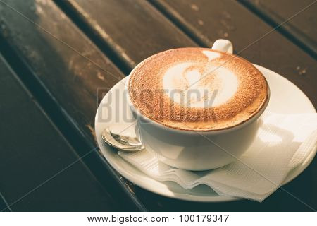 White Cup Of Cappuccino With Cinnamon On A Wooden Table In A Cafe