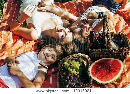 cute happy family on picnic laying on green grass mother and kids