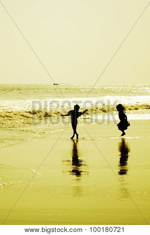 Two children dancing on the beach at sunset