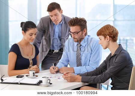 Business team meeting at office table with boss. Writing on paper, wearing suit and glasses, sitting at table, businessman, businesswoman, personal organizer, morning coffee.