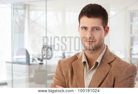 Closeup portrait of smiling young businessman at bright office.