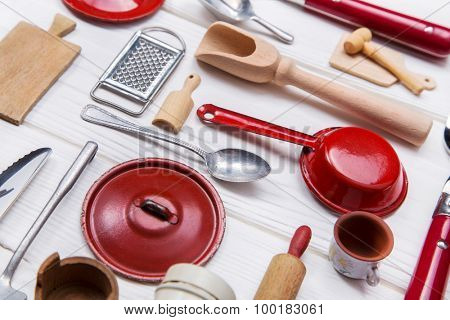 Old red white doll's kitchen miniatures of tin and wood. Vintage cooking decoration for restaurants and gastronomy.