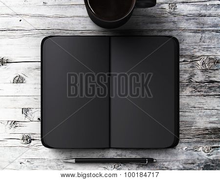 Blank Black Diary With Pen And A Cup Of Coffee On A Wooden Table