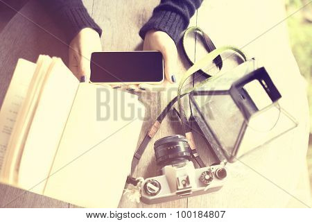 Girl's Hands With Cell Phone, Old Camera And A Book On A Wooden Table
