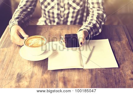 Girl Hands With Cell Phone, Cappuccino And Blank Diary With Pencil On A Wooden Table