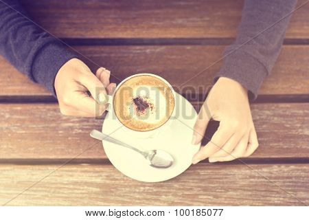 Girl Holding A Cup Of Cappuccino And Wooden Table
