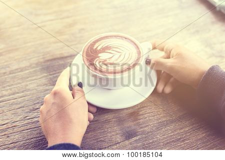 Girl Holding A Cup Of Coffee On A Wooden Table, Vintage Photo Effect