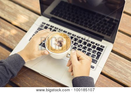 Laptop And Cappuccino On A Wooden Table
