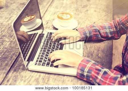 Girl's Hands With Laptop And Coffee Mug On A Wooden Table