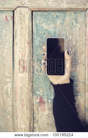 Girl Holding Cell Phone And Vintage Wooden Wall