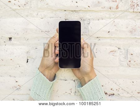 Girl Holding Cell Phone And On A Brick Wall Background