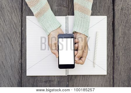 Girl Hands With Cell Phone, Blank Diary And A Pencil On A Wooden Table