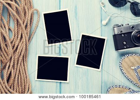 Travel and vacation photo frame and items on wooden table. Top view. Toned