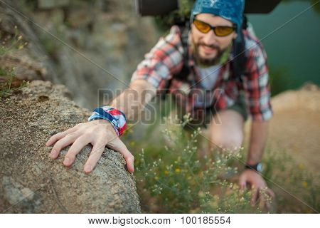 Young caucasian man with backpack climbing the rock