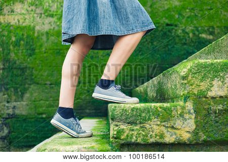 Woman Walking Up Stairs Covered In Moss