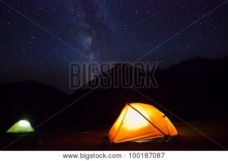 milky way above the mountains with tent highlighted