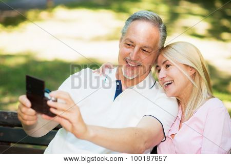 Portrait of a mature couple using a digital camera to take a self portrait in a park