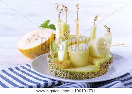 Melon ice lolly on white wooden background