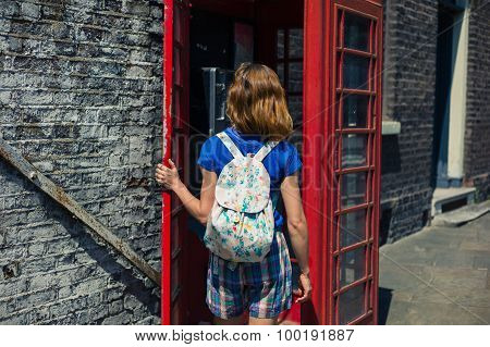 Young Woman Entering A Phone Booth