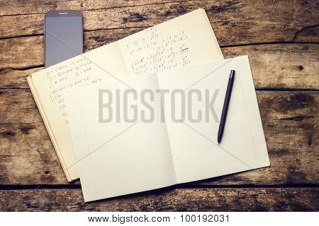 Exercise Book With Smartphone And Pen On Old Wooden Table