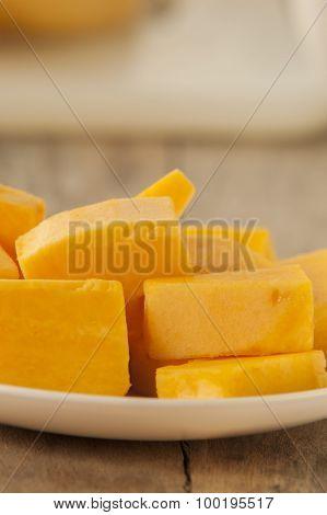 Chopped orange butternut squash close up on wooden background