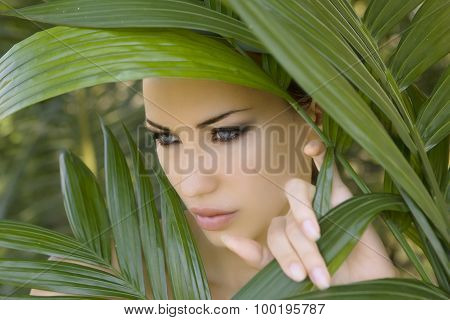 Sexy Beautiful Woman Hiding Behind The Palm Leaves. Beautiful Stylish Woman With Smokey Eyes