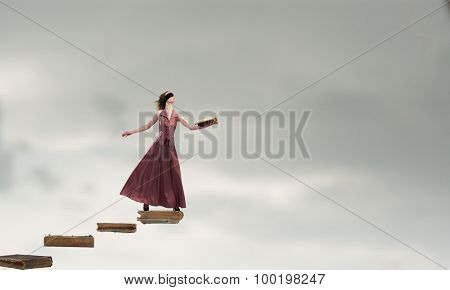 Woman in long dress with blindfold on eyes and book in hand