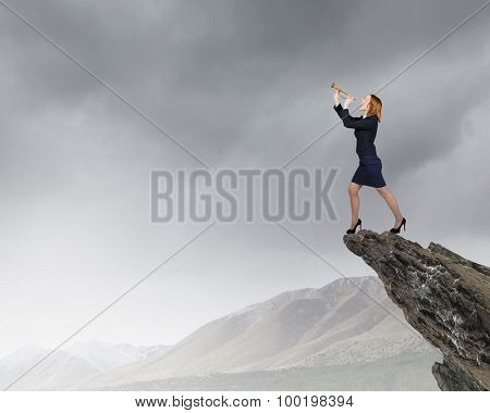 Young businesswoman standing on rock edge and proclaiming something in horn